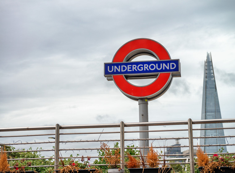 Underground sign against cloudy sky and The Shard