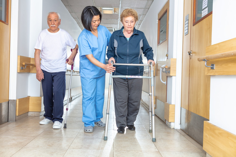 Elderly woman with crutches in rehab clinic