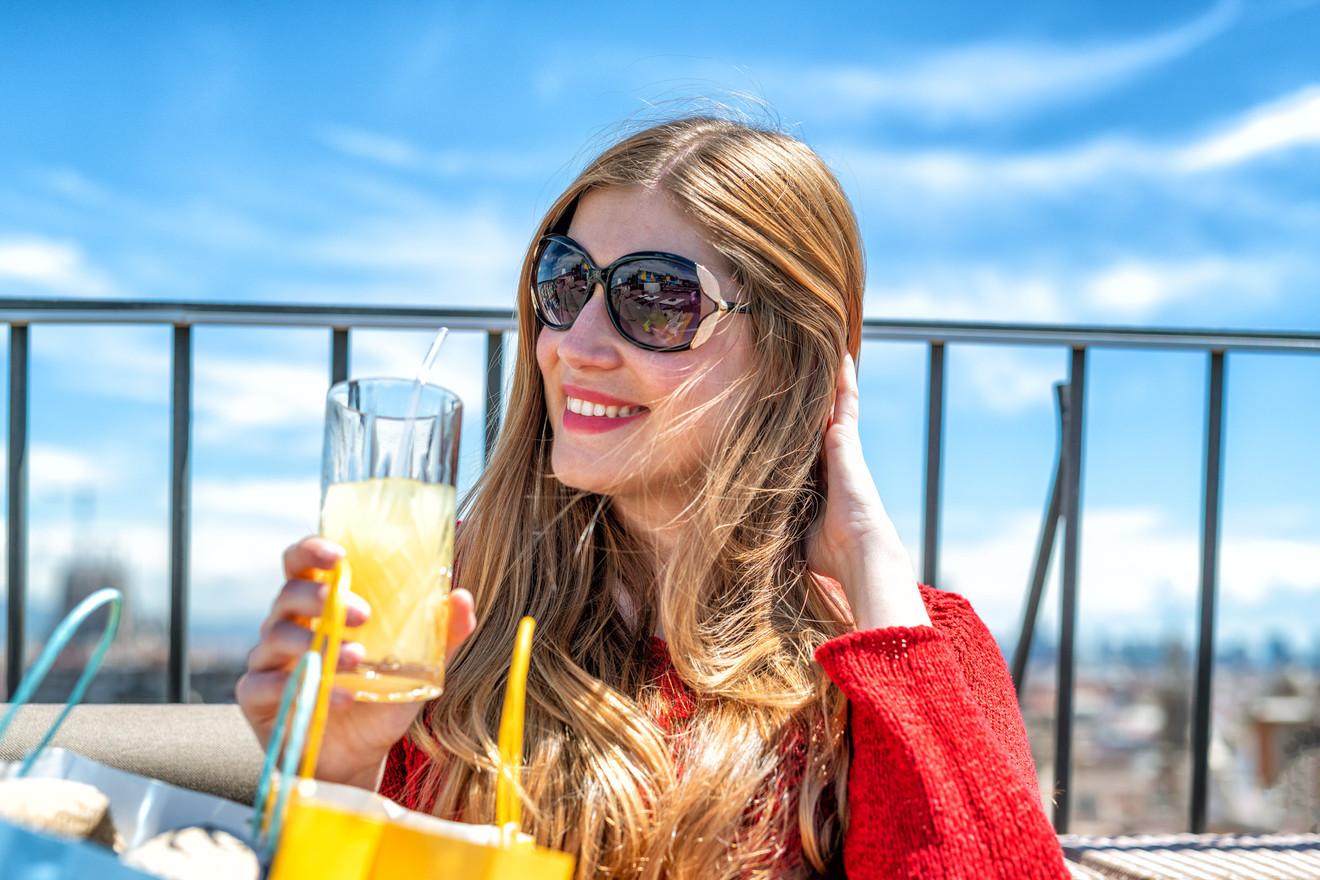 Blonde girl drinking orange juice on a city rooftop