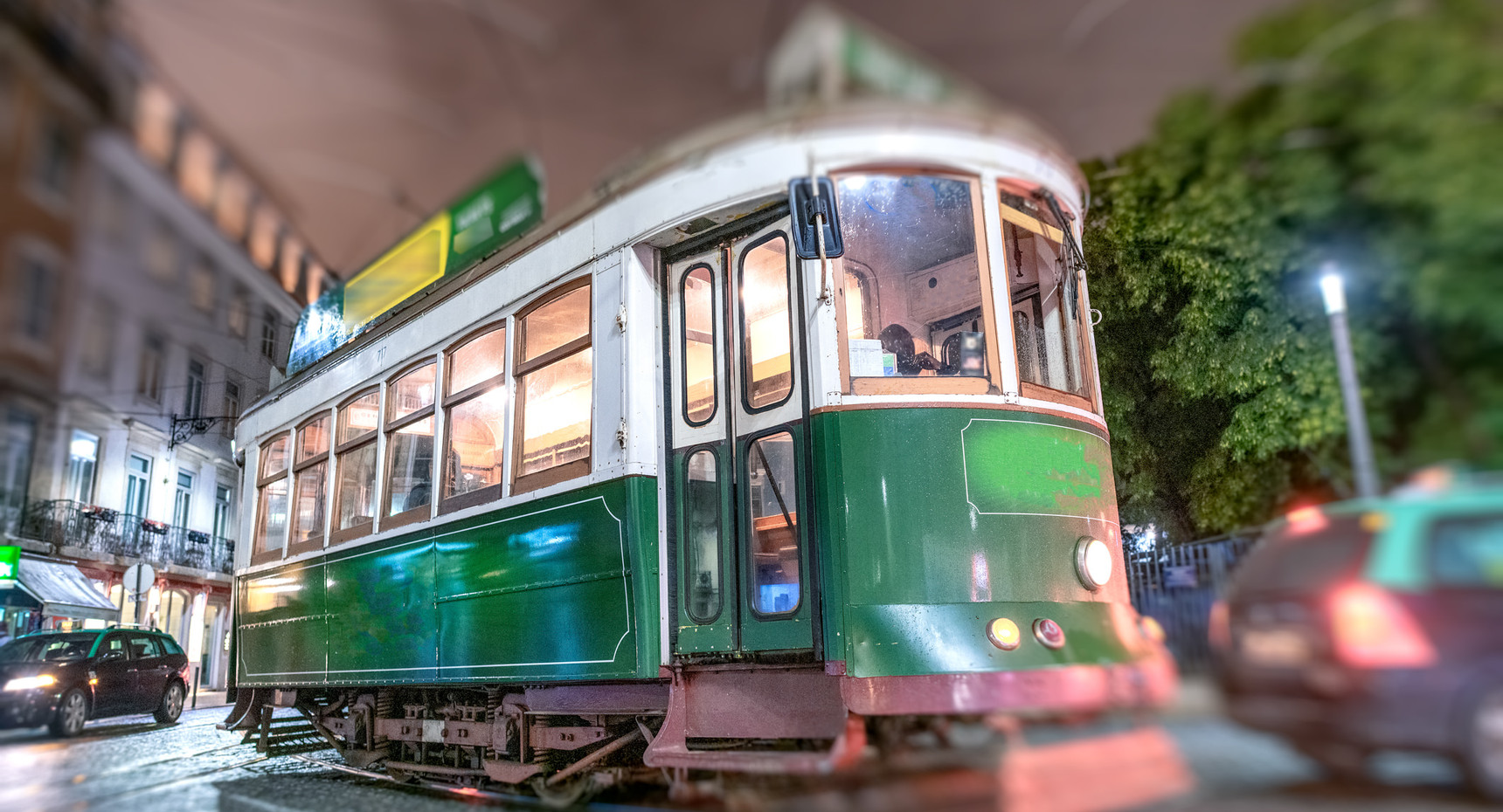 Old green city tram at night