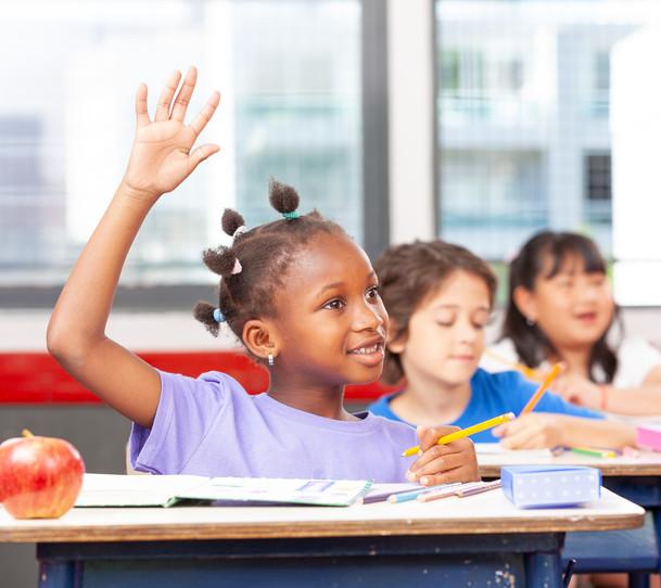 African girl raising hand at elementary school