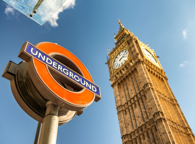 Underground sign against cloudy sky and Big Ben