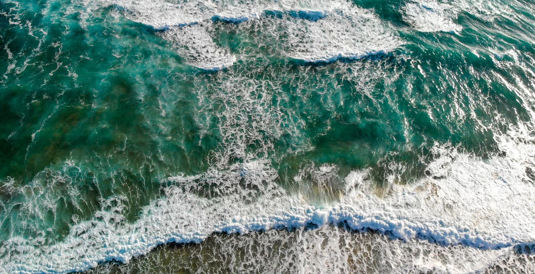 Overhead aerial view of ocean waves on the beach