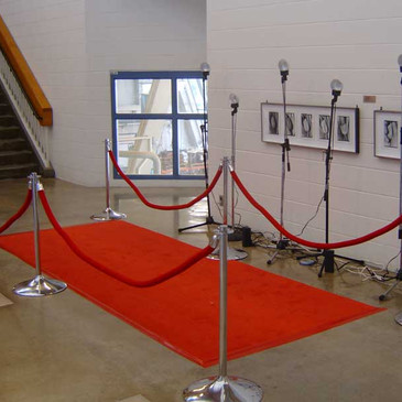 Hoi Polloi 2006   An encounter based installation that deflates the notion of celebrity by giving star power to the masses.    Hoi Polloi uses The Red Carpet as your invitation to celebrity. When you walk Hoi Polloi's red carpet you are greeted by the undulating screams of your fans and the undying devotion of the paparazzi, as they swoon for your attention. Screams of love and hysteria follow your every step. The paparazzi try to get your attention as they to scoop one another in vain attempts to catch a glimpse of your image. Camera flashes blind you as you walk the red carpet. You become the focus of their attention, even for just a moment.