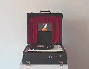 Footlights 2008   Footlights, examines the sound of the audience in a performative setting. In this work the sound of the audiences bodily utterances, coughing and throat clearing become the audio focus. Footlights is contained in a old record player. This player with its open lid is enhanced with a LCD screen surrounded by red velvet theatre style curtains. The turntable has a custom cut record, which the participant is invited to play. On the record are the recorded sounds of an audience's utterances. Footlights, invites the participants to play its record. To do this the spectator is asked to lift the tone arm and pull it to the right where an audible click is heard. This activates both the platter of the record player and video screen mounted in the lid of the same player. The participant then places the needle of the record player on the record and the dancer moves to the sounds of the record  Footlights, is rooted again in the use of an old record player. This player with its open lid is enhanced with a LCD screen surrounded by red velvet theatre style curtains. The turntable has a custom cut record, which the participant is invited to play. On the record are the recorded sounds of an audience's utterances, (coughing and throat clearing). Footlights, invites the participants to play its record. To do this the spectator is asked to lift the tone arm and pull it to the right where an audible click is heard. This activates both the platter of the record player and video screen mounted in the lid of the same player. The participant then places the needle of the record player on the record and the dancer moves to the sounds of the record.