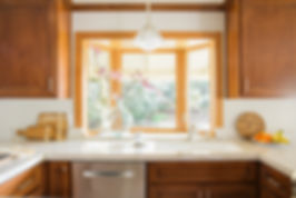 natural medium tone wood kitchen cabinets bay window simple clean design interior danielleidd dani perkins taj mahal quartzite white countertops craftsman style updated remodel craftsman wood tones shape u-shape