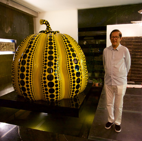 Lito Camacho with a Yayoi Kusama pumpkin sculpture at the entrance of his home.