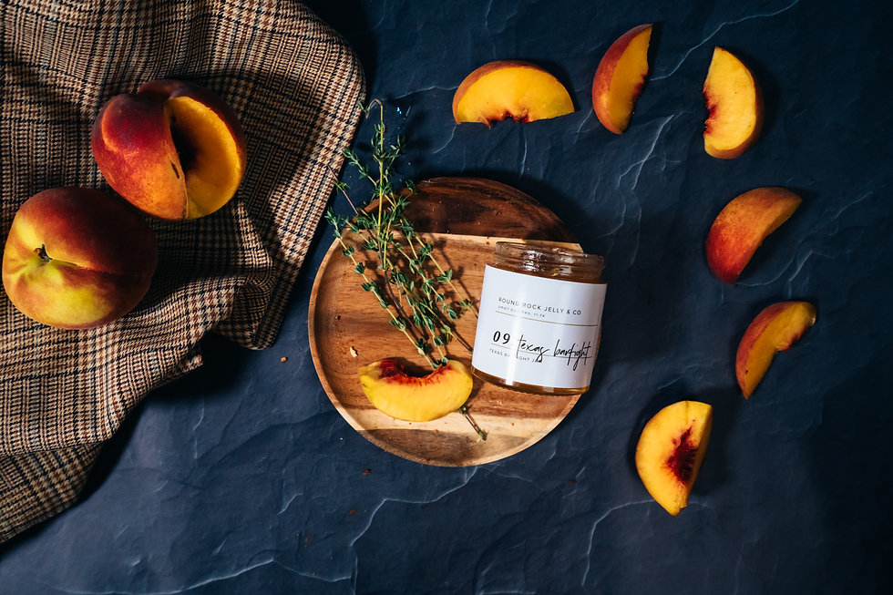 Moody image of peaches styled delicately around a wooden plate. On the plate sits jam and rosemary.