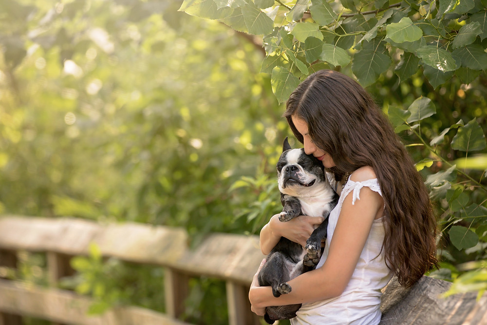 A woman hugs her dog on a bridge.