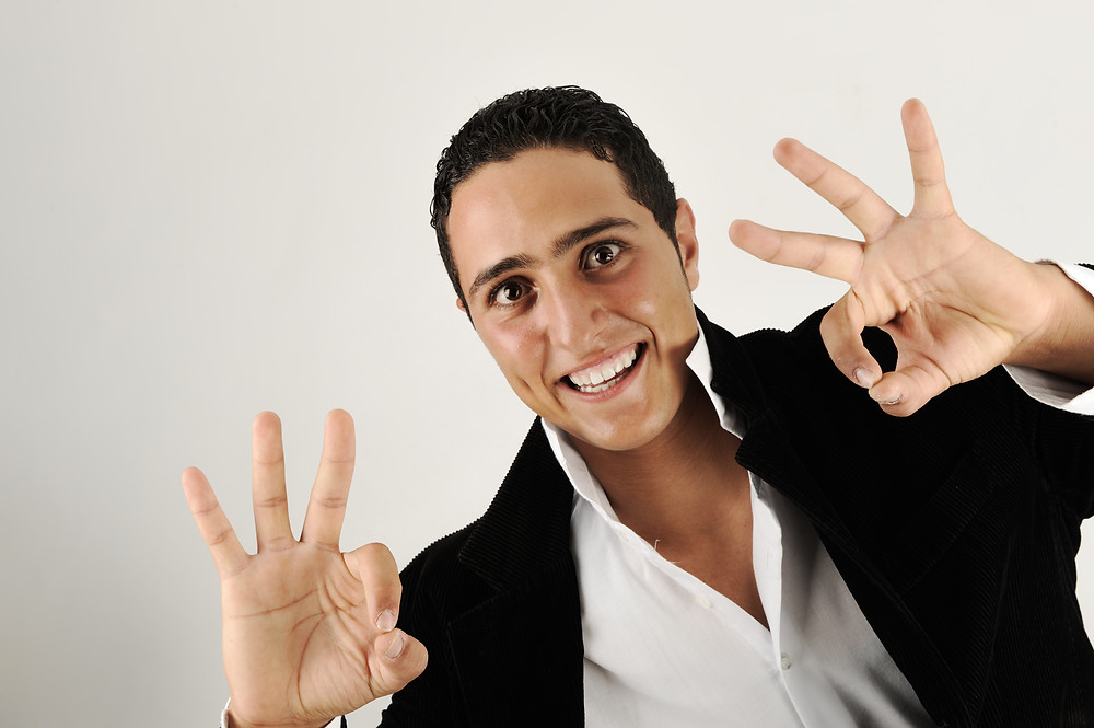 smiling man displaying the ok sign on both hands