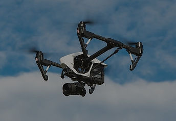 Drone flying in the blue sky with clouds