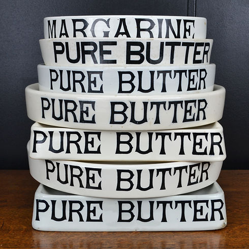 A stack of antique white ironstone Pure Butter grocers slabs