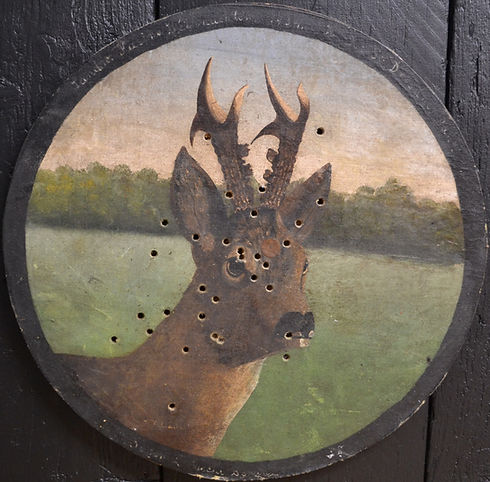 Antique wooden deer plaque used as a target