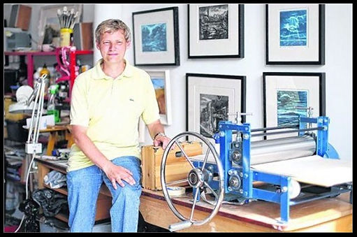 Photograph of the artist Allan Richardson next to his printing press.
