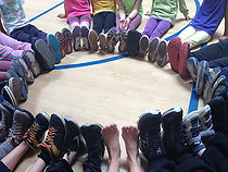 A group of children are sitting in a cirle. The photo is zoomed in on their feet, everyone is wearing shoes except for one person in bare feet. The shoes are of all different sizes and colors, representing community diversity.