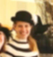 A headshot of Sonja. She is wearing a black bowler hat with a white flower and is wearing a shirt with broad horizontal black and white stripes.