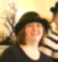 A head shot of Olivia. She is smiling and wearing a black bowler hat and a black t-shirt.