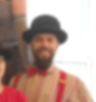 A head shot of Tim. He is wearing a black bowler hat and a colorful striped shirt with a red bow tie and red suspenders. Tim is smiling!