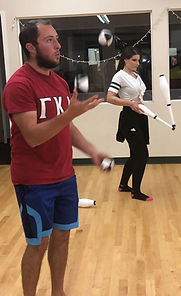 A man juggles balls in the foreground and a woman balances juggling clubs in the background.