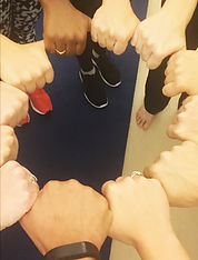 12 hands in fists. Each hand is holding the thumb of the hand next to it and the hands form a circle. The hands are a variety of skin tones. A few have wedding bands.