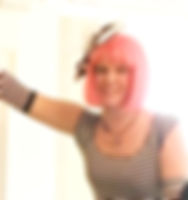 A head shot of Cynthia Rauschert wearing a pink wig with a big bow. She is also wearing a black and white striped t-shirt and she is smiling.