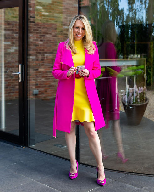 Lizzy standing infront of glass mirror with bright pink coat