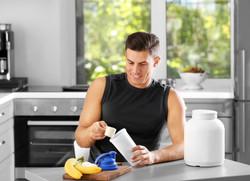 Man preparing protein shake in kitchen.j