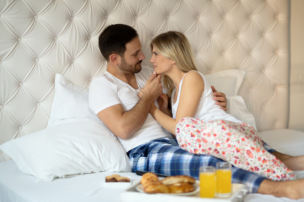 Couple looking lovingly at each other in bed