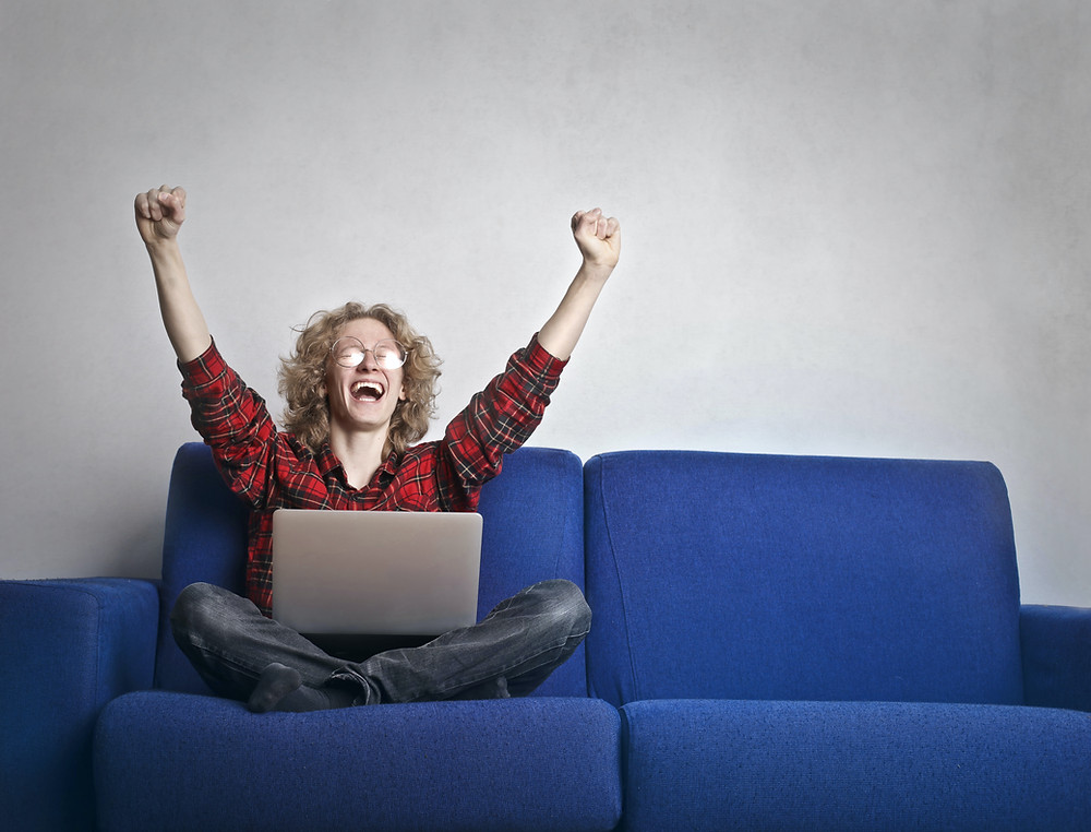 happy woman on computer raising her arms