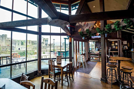 Pub seating area with floor to ceiling windows showing the view of Caerphilly Castle and the outside seating area