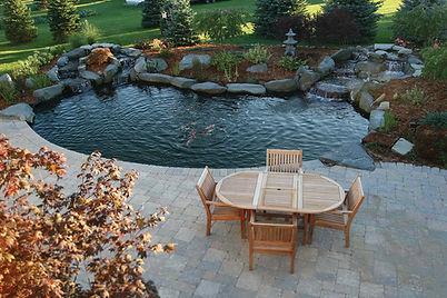 backyard patio and pond with koi fish and waterfall