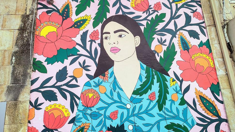 ציור רחוב של אישה וסביבה פרחים