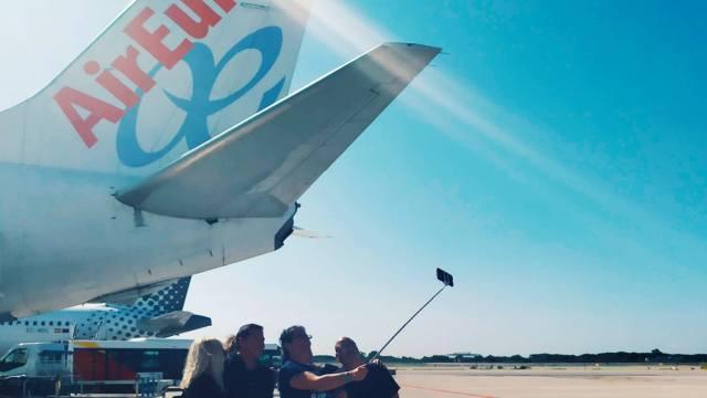 אנשים מצטלמים בשדה תעופה ליד מטוס חונה