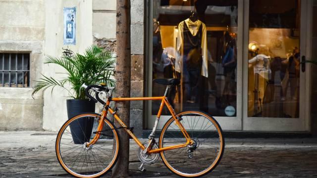 אופניים כתומים מונחים על עמוד וברקע חלון ראווה של חנות בגדים