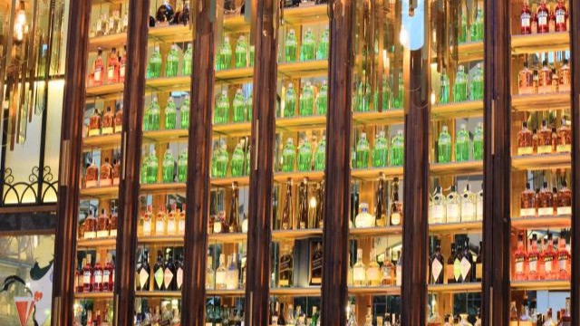 ארון גבוה מלא בקבוקי זכוכית צבעוניים