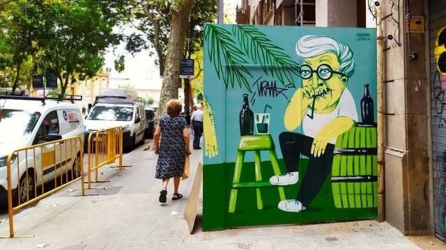 אנשים הולכים ברחוב וציור קיר של אדם ליד בקבוק משקה