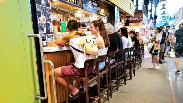 אנשים יושבים במסעדה בתוך השוק