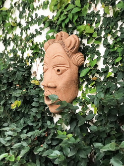 ceramic mask on courtyard wall