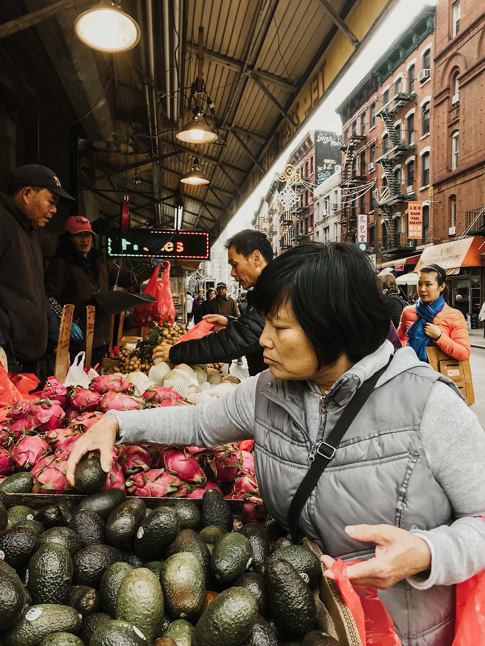 woman grocery shopping for avocados at an outdoor market