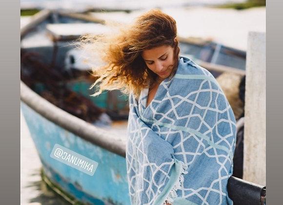 דוגמנית מתעטפת במגבת חוף כחולה ונשענת על סירה