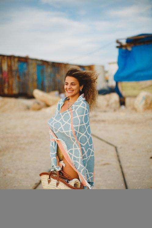 בחורה מתכסה במגבת חוף בצבע תכלת