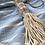 שרשרת עשויה 5 קונכיות עם חבל טבעי מונחת על סדין