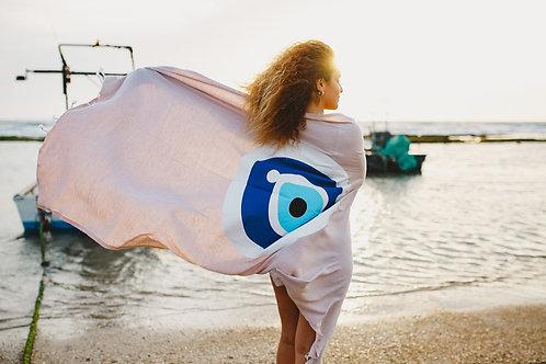 דוגמנית הבית מתעטפת במגבת חוף עם ציור עין כחולה