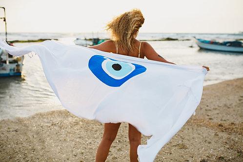 בחורה מתעטפת במגבת חוף עשויה בד בצבע לבן