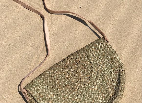 תיק אנדמן עשוי קש מונח בחוף הים