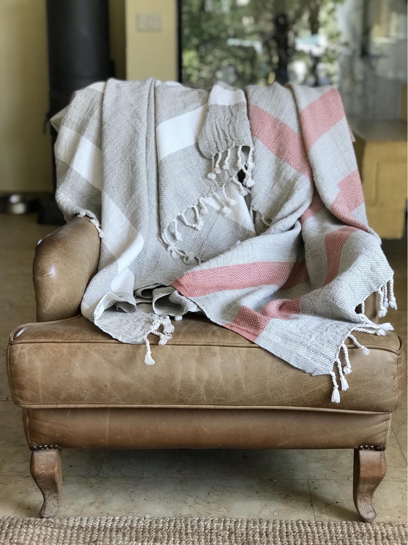 שמיכות מפוזרות על ספה בצבע חום