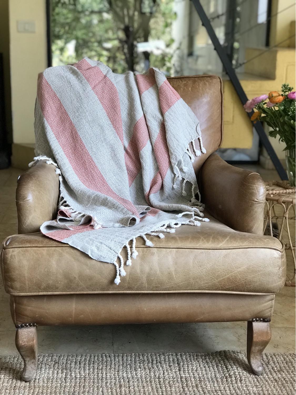 שמיכת כרבול עשויה פשתן עם פסים אדומים מונחת על הספה