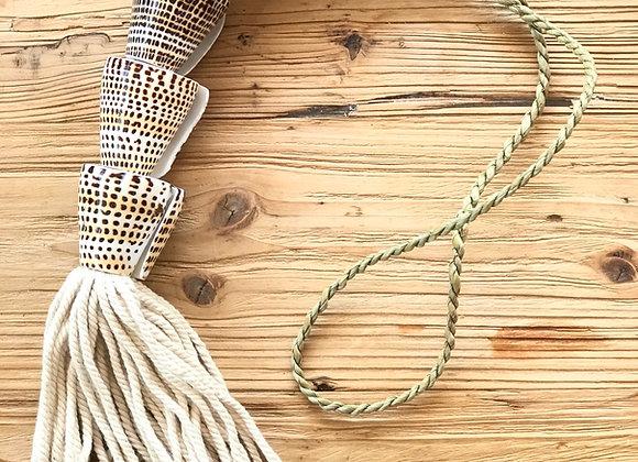 שרשרת עשויה קונכיות עם חבל טבעי מונחת על הפרקט