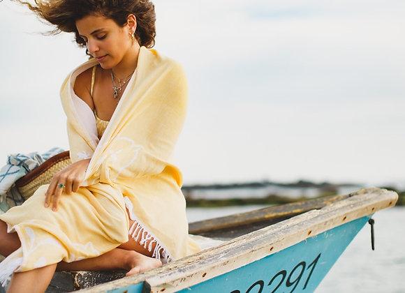 בחורה יושבת על סירה ומתעטפת במגבת חוף צהובה