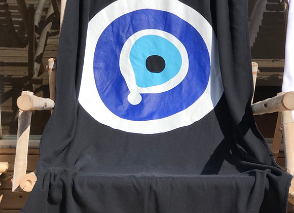 מגבת חוף שחורה עם ציור עין כחולה פרוסה על כיסא חוף